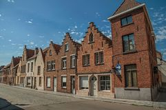Brick facade of old houses with a blue sunny sky in an empty street of Bruges. With many canals and old buildings, this graceful town is a World Heritage Site Stock Photos