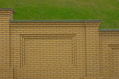 Brick fence. A fragment of a fence made ​​of yellow brick with green grass in the background Royalty Free Stock Image