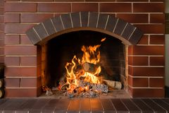 A brick fireplace in which a fire burns. Firewood and hot coals burn in a brick fireplace with bright fire Royalty Free Stock Image