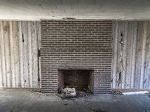 Brick fireplace with wood paneling Stock Photography