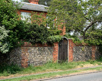 Brick and Flint Wall. Old Brick and Flint Wall and Wooden Gate to an English Rural House Royalty Free Stock Photos
