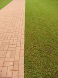 Brick footpath next to grass Stock Photo