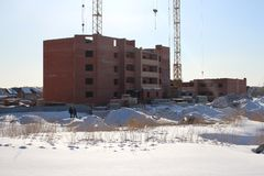The brick Foundation of a building under construction crane in winter royalty free stock images