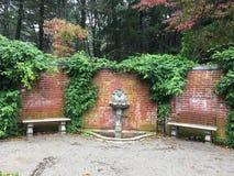 Brick fountain scene. Hedges fountain brick wall Royalty Free Stock Photos