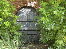 Brick Frame Wooden Door/Gate. Arch wooden door/gate framed by red brick surrounded by green shrubs Stock Image