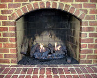 Brick gas fireplace. Close up of brick gas fireplace with a lit fire Royalty Free Stock Photos