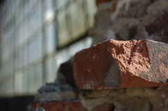 Brick and glass. Partially torn down brick wall exposing large glass window wall in background Royalty Free Stock Photo