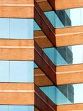Brick and Glass Architectural Angles. Modern building with mirrored glass and bricks with eye catching reflecting angles stock images