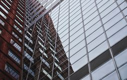 Brick and glass building reflection. A brick and glass building reflects a gray sky above Stock Photography