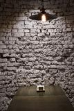 Brick grunge wall and ceiling lamp above table. Brick grunge wall and ceiling lamp, above table. Rough grey background, Hang light bulb illuminate dining place Royalty Free Stock Photography