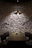 Brick grunge wall and ceiling lamp above table. Brick grunge wall and ceiling lamp, above table. Rough grey background, Hang light bulb illuminate dining place Royalty Free Stock Image