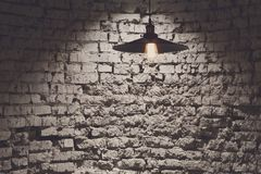 Brick grunge wall and ceiling lamp, copy space. Rough grey background, Hang light bulb illuminate part of side Royalty Free Stock Image