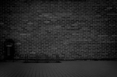 Brick grunge weathered black wall background with walkway and garbage can Stock Images