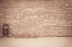 Brick grunge weathered brown wall background with walkway and garbage can Royalty Free Stock Photo