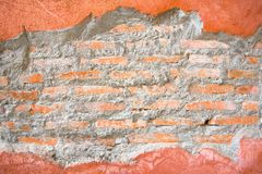 Brick hole in a orange concrete wall frame. Conceptual background texture Royalty Free Stock Photo