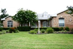 Brick Home. Modest buff brick home with tropical landscaping, green lawn and arched Royalty Free Stock Photos