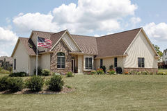 Brick home with American flag Stock Photos