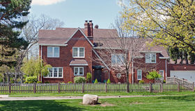 Brick Home with Natural Wood Picket Fence. Large. red, brick home in urban neighborhood with natural wood, picket fence & grape harbor to side & rock in front Stock Images