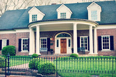 Brick Home with Rounded Front Porch. A beautiful, southern brick home with black shutters and a rounded front porch with pillars and a black iron fence royalty free stock image