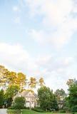 Brick Home Under Pleasant Skies. A nice brick home in landscaped lawn under pleasant summer skies Royalty Free Stock Photo