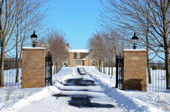 Brick home in winter. Luxury brick home with long driveway in winter Royalty Free Stock Images