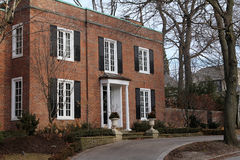 Brick house with black shutters. Typical classically styled older middle class frame home in a suburb Stock Photography