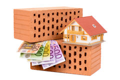 Brick for house construction and Euro. Money with model house Royalty Free Stock Photos