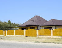 Brick house with corrugated metal profile roof and wooden fence. Beautiful view of the facade. Style of design Royalty Free Stock Images