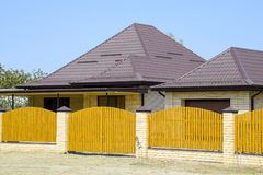 Brick house with corrugated metal profile roof and wooden fence. Beautiful view of the facade. Style of design Stock Photo