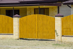 Brick house with corrugated metal profile roof and wooden fence. Beautiful view of the facade. Style of design Stock Photography