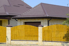 Brick house with corrugated metal profile roof and wooden fence. Beautiful view of the facade. Style of design Stock Image