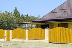 Brick house with corrugated metal profile roof and wooden fence. Beautiful view of the facade. Style of design Stock Images