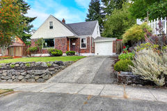 Brick house with curb appeal. Cozy house with brick trim and front yard landscape Stock Photography