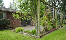 Brick house exterior backyard with patio and roses. Royalty Free Stock Photography