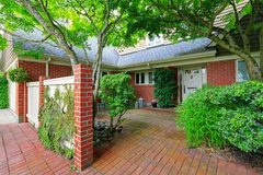 Brick house exterior with tile floor front yard Royalty Free Stock Image