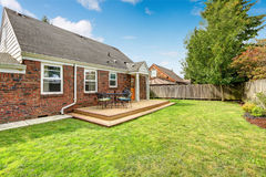 Brick house exterior with walkout wooden deck. And patio area with barbecue royalty free stock image