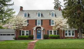 Brick House with Flowering Dogwood Trees Royalty Free Stock Photography