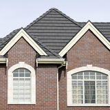 Brick House Home Exterior Tile Roof. Section of a red brick home showing the roof details stock image