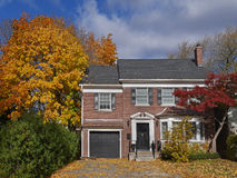 Brick house with maple tree and fall colors. Middle class two storey brick house with maple tree and fall colors royalty free stock photo