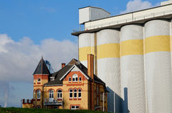 Brick house near store silos for grain Royalty Free Stock Photo