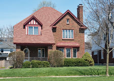 Brick House with Red Shingle Roof Stock Photo