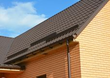 Brick house rooftop with metal roof, rain gutter pipeline and waterproofing in problem corner area. Roofing construction. Close up stock photo