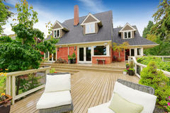 Brick house with walkout deck. Patio area with wicker chairs Royalty Free Stock Image