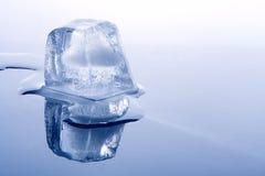 Brick of ice on blue Stock Photos