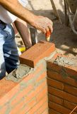 Brick Layer 2. A brick layer levels his bricks as he builds a wall Stock Images