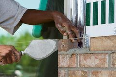 Brick Layer. African American worker lays a row of bricks using cement mortar and a trowel at a new house under construction Royalty Free Stock Photo