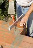 Brick layer 3. A brick layer taps on the bricks to put them in place Stock Photography