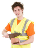 A brick layer with a brick. A builder holding a tool and a brick smiling, isolated on white Royalty Free Stock Image