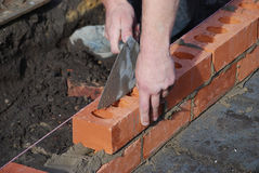 Brick layer. Bricklayer using trowel to tap a brick level Stock Photos