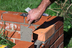 Brick layer, frame for compost. Brick wall as a border for the compost pile Stock Photos